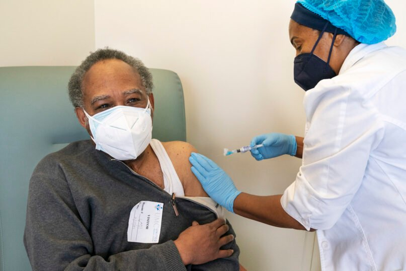 In this Wednesday, Feb. 10, 2021, photo the Rev. James Coleman, 70, is vaccinated for COVID-19 by nurse practitioner Ifreke Udodong at United Medical Center in southeast Washington. (AP Photo/Jacquelyn Martin)