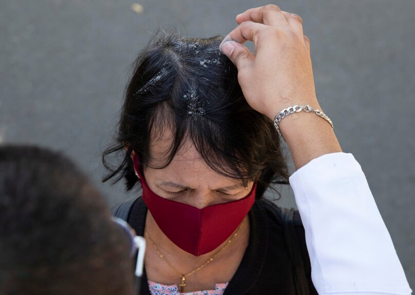 In this Feb. 26, 2020, file photo, a Catholic devotee has ash sprinkled on her head during Ash Wednesday rites in Manila's Paranaque, Philippines. Sprinkling ash on the head of devotees, instead of using it to mark foreheads with a cross, is one strategy to avoid physical contact during the pandemic. (AP Photo/Aaron Favila, File)