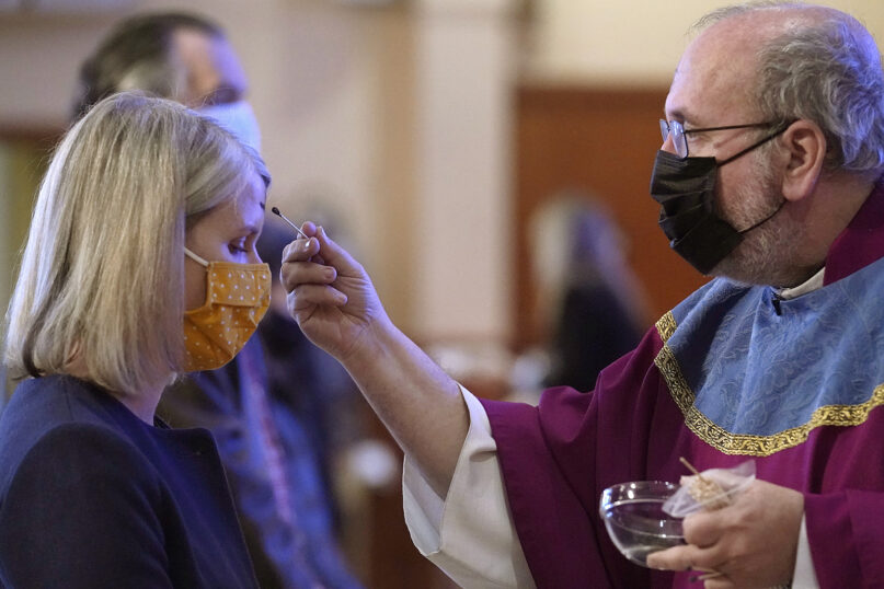 The Rev. Paul Soper, right, uses a swab to apply ash to the forehead of a parishioner during Ash Wednesday Mass at St. Margaret Mary Parish in Westwood, Massachusetts, on Feb. 17, 2021. (AP Photo/Steven Senne)