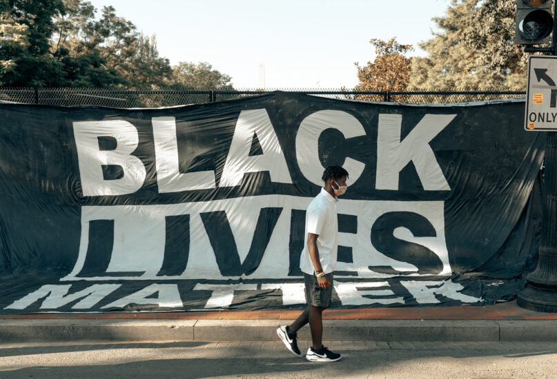An individual passes a Black Lives Matter sign in Washington, D.C. Photo by Clay Banks/Unsplash/Creative Commons