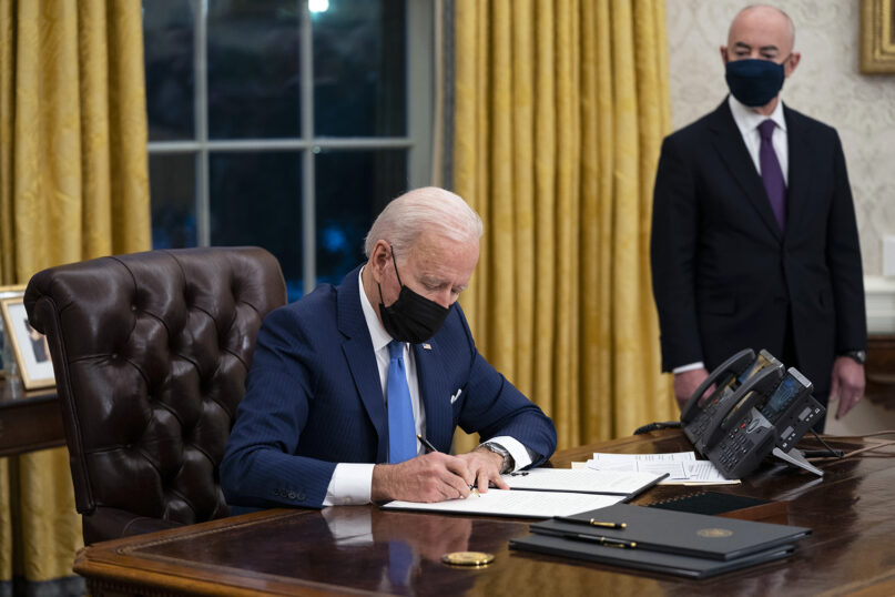 Secretary of Homeland Security Alejandro Mayorkas looks on as President Joe Biden signs an executive order on immigration, in the Oval Office of the White House, Feb. 2, 2021, in Washington. (AP Photo/Evan Vucci)