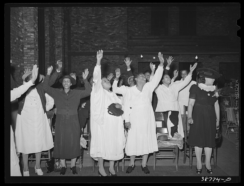 """Members of a Pentecostal church raise their hands in worship, as seen in """"The Black Church: This is Our Story, This is Our Song"""" on PBS. Photo courtesy Library of Congress/Creative Commons"""
