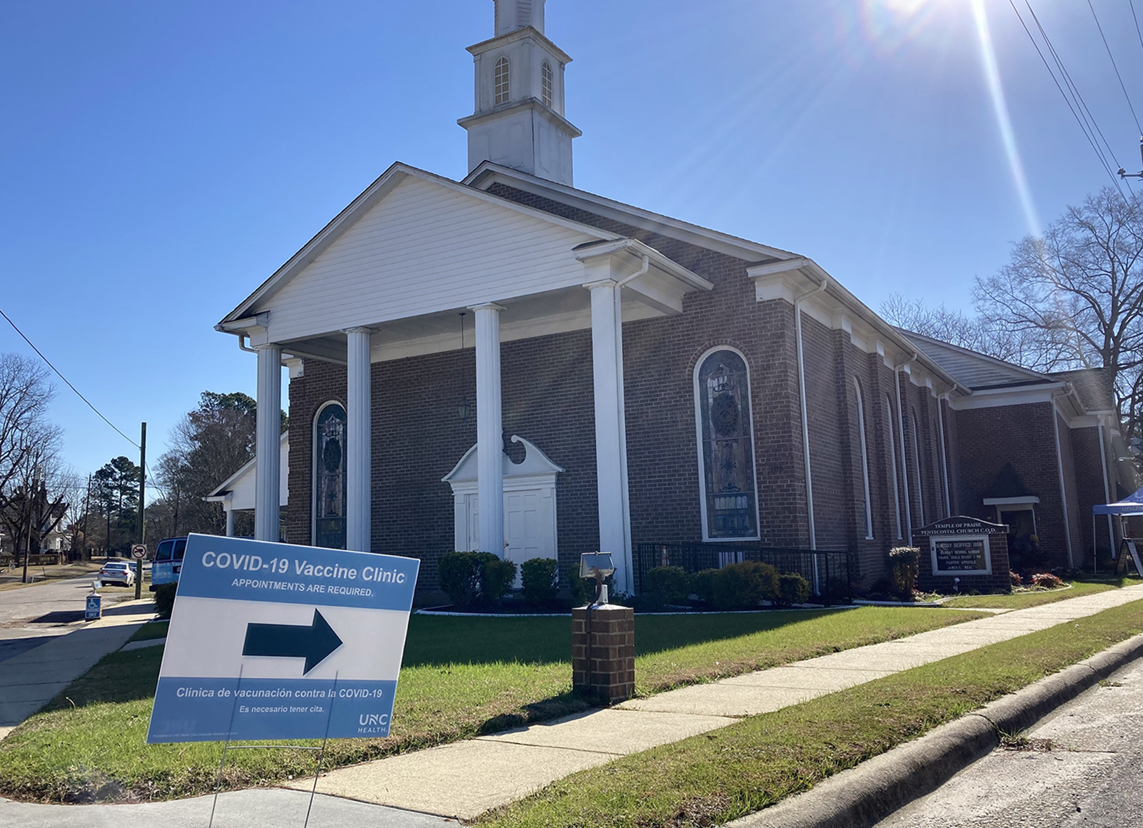 A sign directs people to the side door of the Temple of Praise Church of Deliverance in Kenly, North Carolina, where UNC Health held a mobile vaccination clinic on Wednesday, Feb. 17, 2021. RNS photo by Yonat Shimron