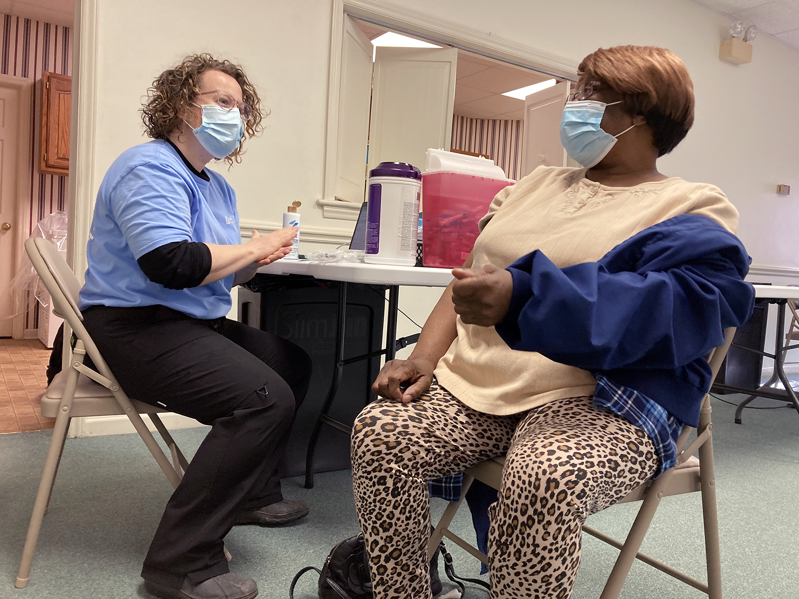 Nurse practitioner Monika Trogdon, left, asks Shirley Hill some questions before giving her a Moderna COVID-19 vaccine shot at a UNC Health mobile clinic at a Kenly, North Carolina, church on Wednesday, Feb. 17, 2021. RNS photo by Yonat Shimron