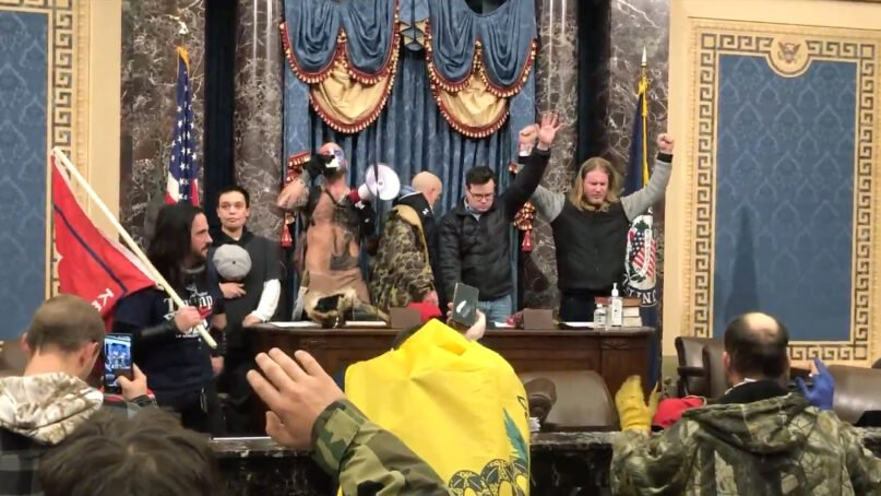 A group of insurrectionists pray inside the U.S. Senate chamber after breaching the Capitol, Jan. 6, 2021, in Washington. Video screengrab via Luke Mogelson/The New Yorker