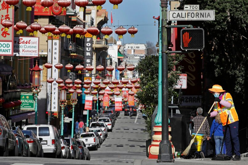 FILE - In this Jan. 31, 2020, file photo, a masked worker cleans a street in the Chinatown district in San Francisco. Police are stepping up patrol and volunteers are increasing their street presence after several violent attacks on older Asians stoked fear in the San Francisco Bay Area's Chinatowns. (AP Photo/Ben Margot, File)