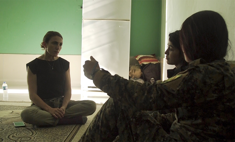 """Author Gayle Tzemach Lemmon, left, interviews a group of women fighters during the fight for Raqqa in the summer of 2017. Photo courtesy of """"The Daughters of Kobani"""""""