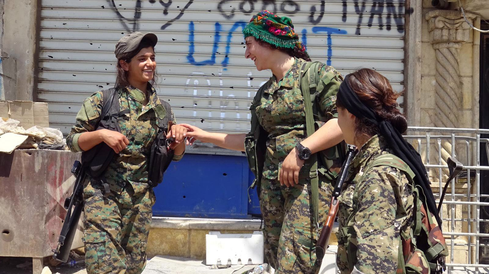 """A group of fighters, part of an all-female Kurdish militia, share a laugh. Photo courtesy of """"The Daughters of Kobani"""""""
