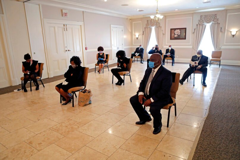 In this April 22, 2020, file photo, friends and family of Larry Hammond — who were among only 10 mourners allowed — sit in chairs spaced for social distancing during his funeral at Boyd Funeral Home in New Orleans. (AP Photo/Gerald Herbert, File)