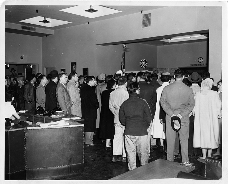 A Mass is celebrated at the General Electric factory in Bridgeport, Conn., in Feb. 1956. A noon Mass was celebrated every Wednesday during Lent for employees at the plant. In this photo, an overflow crowd stands outside the auditorium while a Mass is said inside. Officials of G.E. said similar arrangements were in effect at three other of the company's plants--in Burlington, VT., and Lynn and West Lynn, Mass. RNS archive photo by Alan Reid. Photo courtesy of the Presbyterian Historical Society