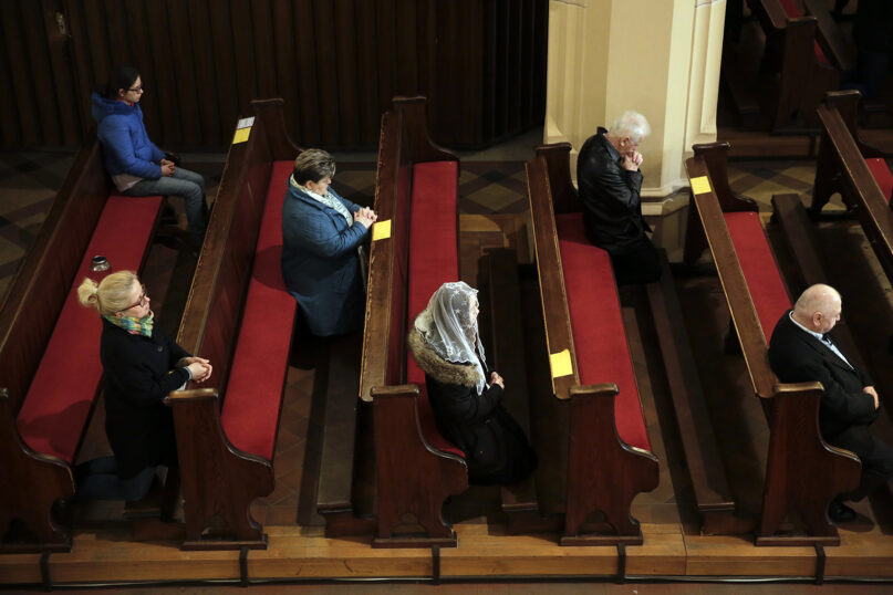 Catholics socially distance while worshipping  at St. Afra Church in Berlin, Germany, Sunday, April 5, 2020. (AP Photo/Markus Schreiber)