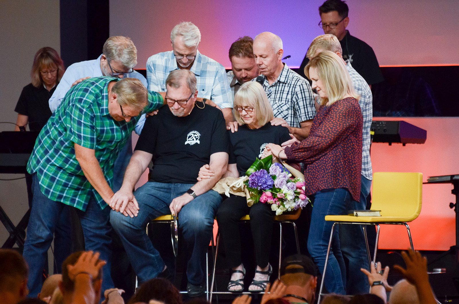 Pastor Rick Warren, left, and other pray over John and Cheryl Baker, seated, during the West Coast Celebrate Recovery Summit at Saddleback Church in Lake Forest, California, on Aug. 12, 2016. Photo by Dave Maurer, courtesy of Saddleback Church