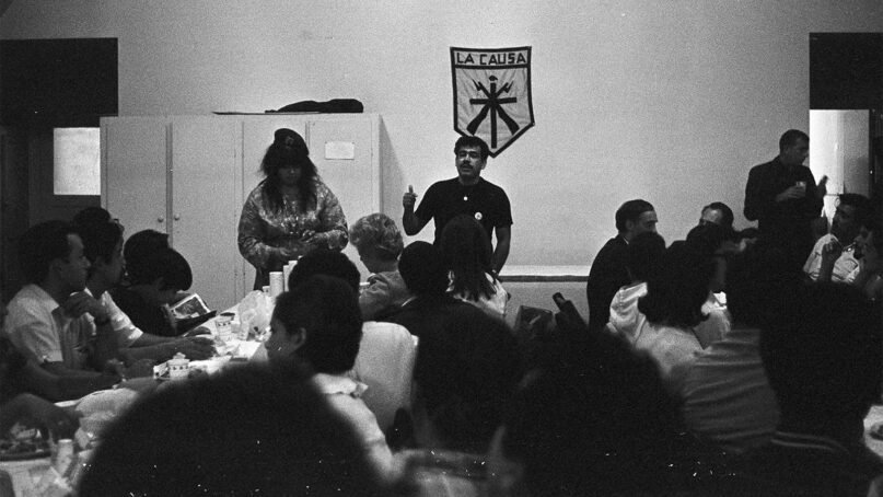 """Chicano organizer Rodolfo """"Corky"""" Gonzales, center, speaks during a lunch gathering at the Church of the Epiphany in Nov. 1968. A """"La Causa"""" (The Cause) banner hangs behind him. ©"""