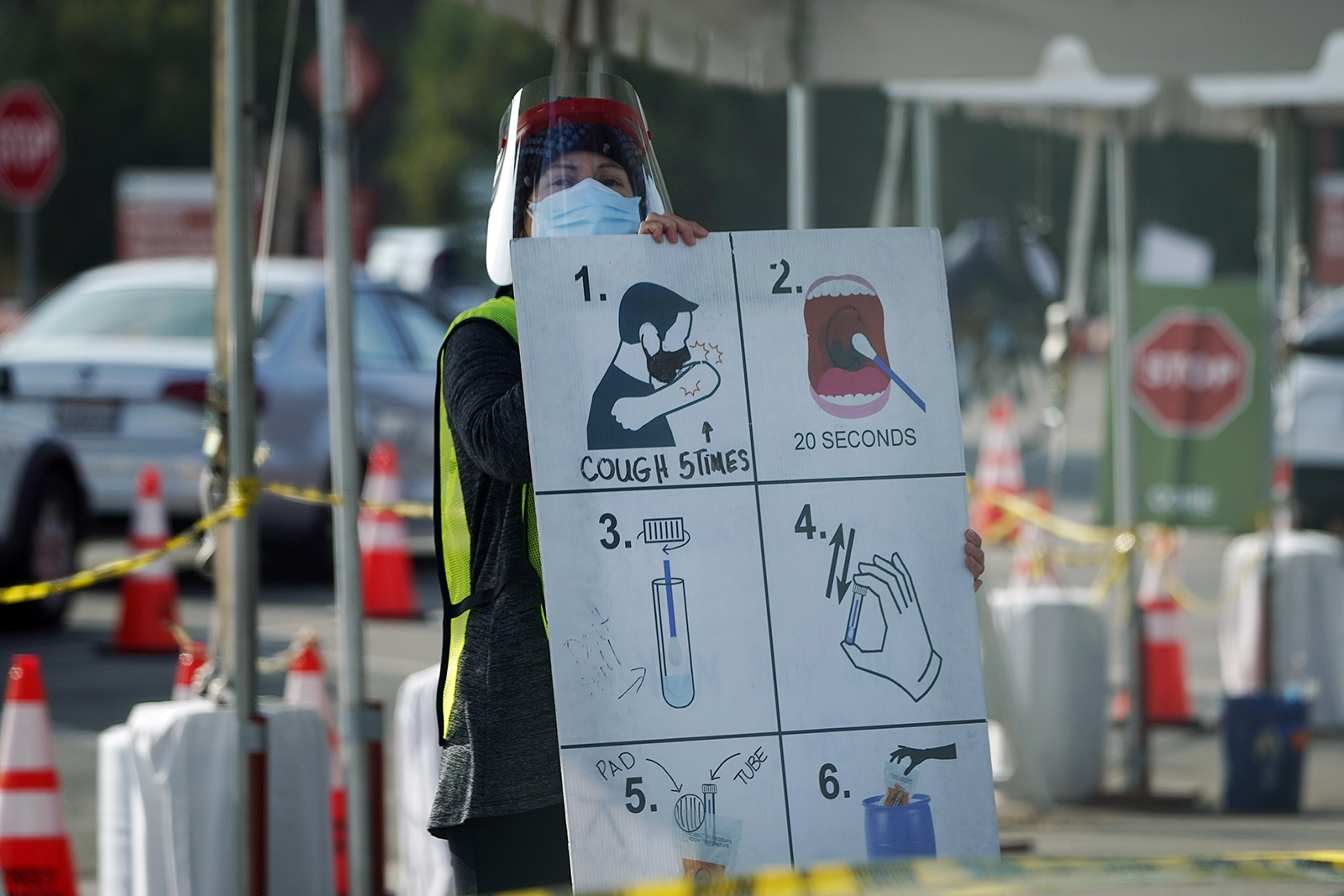 In this Jan. 5, 2021 file photo, a worker gives instructions to motorists at a drive-thru COVID-19 testing site in Los Angeles. (AP Photo/Marcio Jose Sanchez)