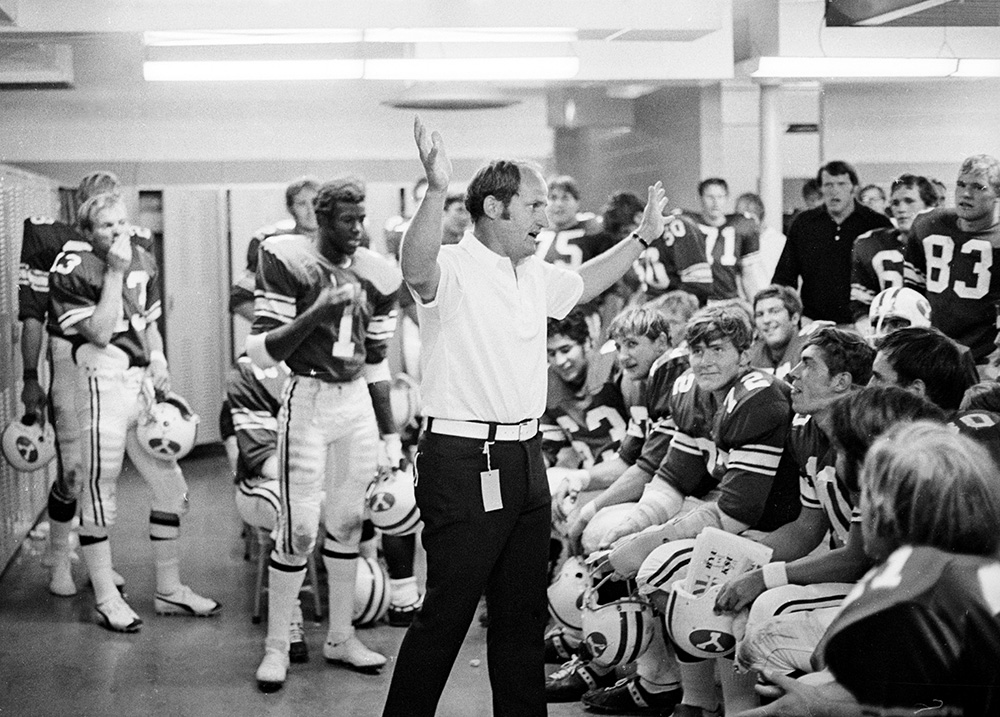 Coach LaVell Edwards, center, in the locker room with his BYU team during his frist game as head coach on September 16, 1972, against Kansas State. © BYU Photo