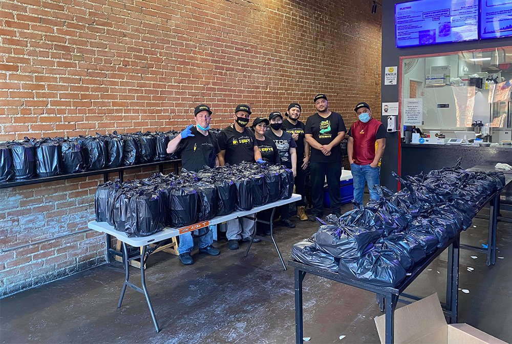Staff at Big Guys Chicken and Rice, a halal restaurant in Dallas, pose with emergency hot meals prepared for storm victims. Photo courtesy of Big Guys