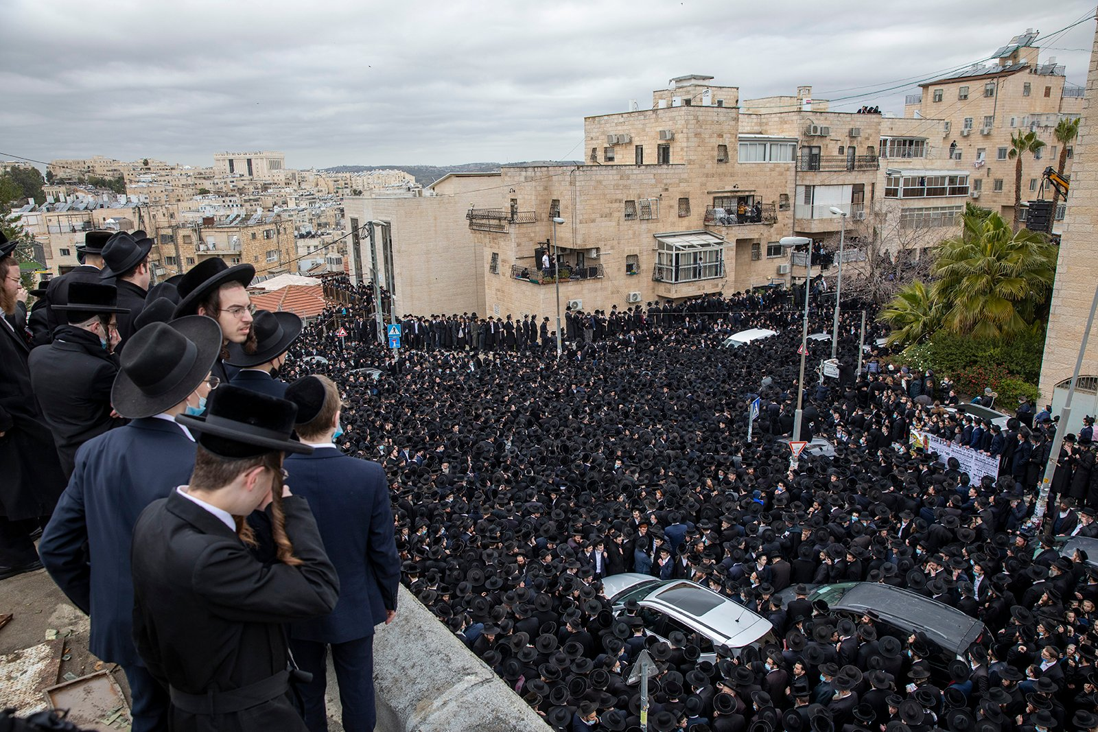Thousands of ultra-Orthodox Jews participate in a funeral for prominent rabbi Meshulam Soloveitchik, in Jerusalem, Sunday, Jan. 31, 2021. The mass ceremony took place despite the country's health regulations banning large public gatherings, during a nationwide lockdown to curb the spread of the virus. (AP Photo/Ariel Schalit)