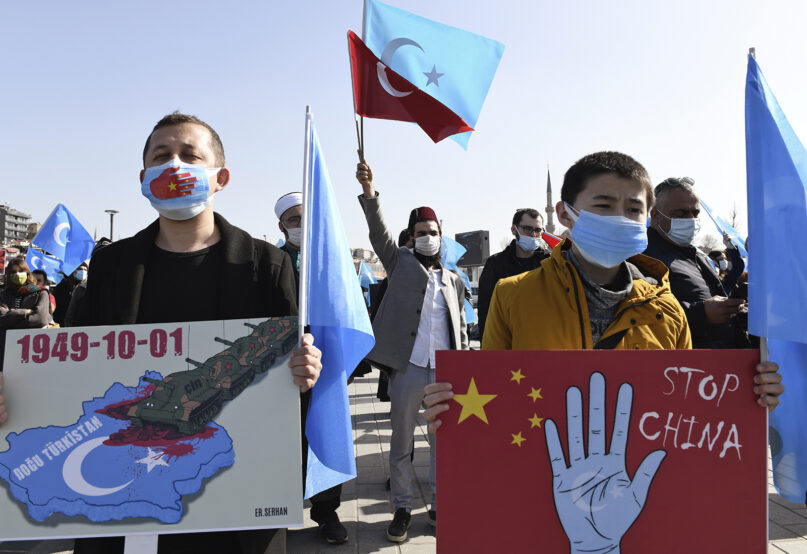 Members of the Uyghur community living in Turkey hold banners while protesting against China, in Istanbul, Friday, Feb. 26, 2021. More than a million Uyghurs and other largely Muslim minorities have been swept into prisons and detention camps in China, in what China calls an anti-terrorism measure. Uyghurs, a Turkic group native to China's far west Xinjiang region, have sought refuge in Turkey for decades because of their shared cultural ties with the country. (AP Photo/Omer Kuscu)