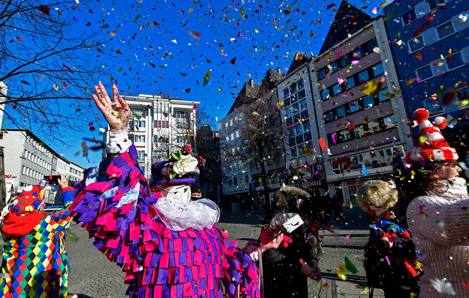 """Just a few people in costumes come together at the """"Alter Markt,"""" where normally tens of thousands of revelers dressed in carnival costumes would celebrate the start of the street carnival, in Cologne, Germany, Thursday, Feb. 11, 2021. This year all carnival celebrations are banned due to the coronavirus pandemic. (AP Photo/Martin Meissner)"""
