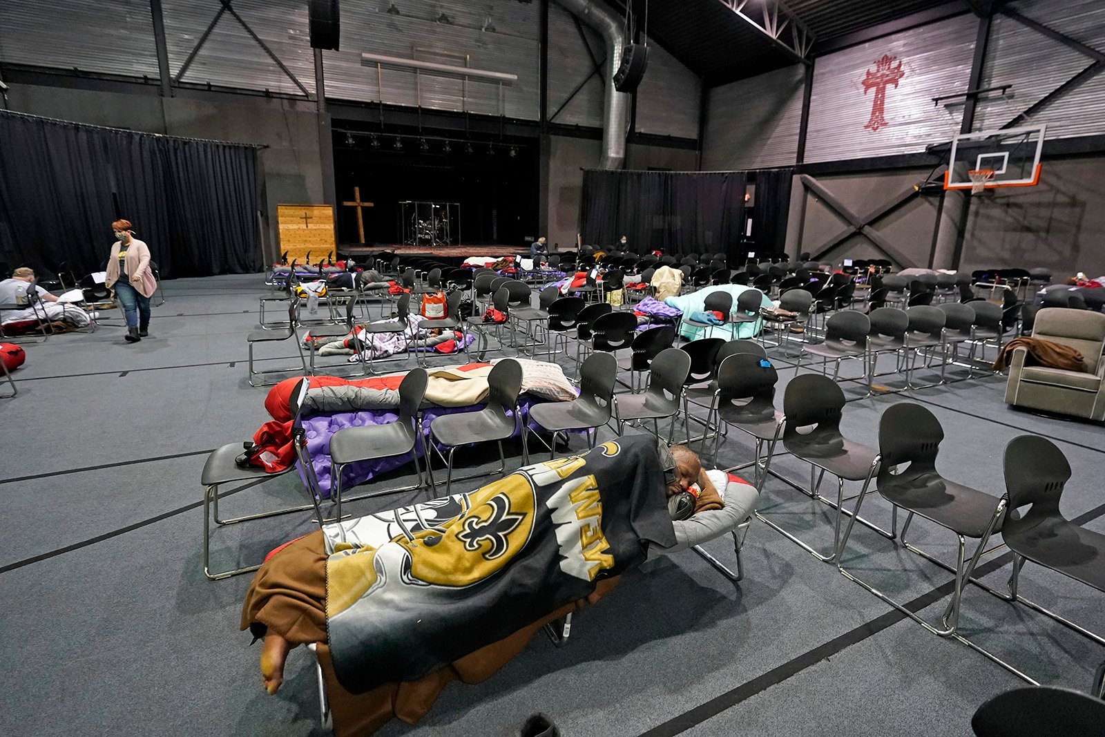 People seeking shelter from below freezing temperatures rest inside a church warming center, Tuesday, Feb. 16, 2021, in Houston. (AP Photo/David J. Phillip)