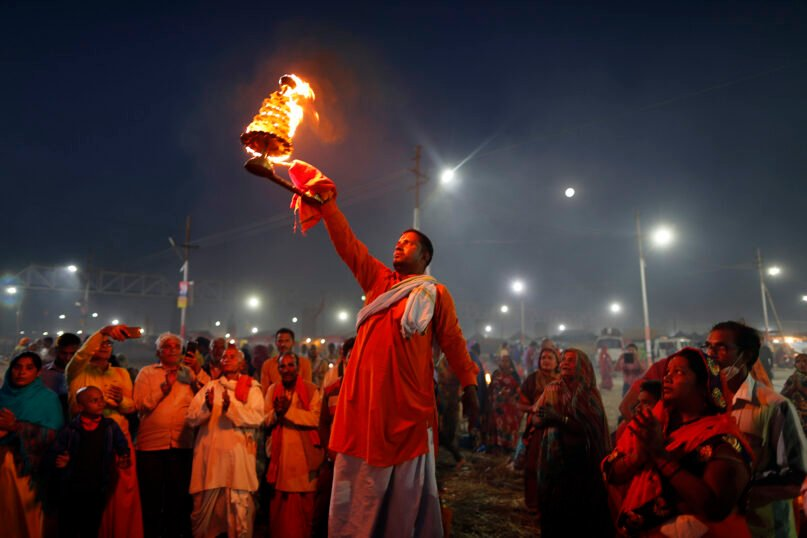 A Hindu priest performs rituals at the Sangam, confluence of the rivers Ganges, Yamuna and mythical Saraswati, on the eve of the Maghi Purnima, or the full-moon day, during the annual traditional fair of Magh Mela in Prayagraj, India,  Feb. 26, 2021. (AP Photo/Rajesh Kumar Singh)