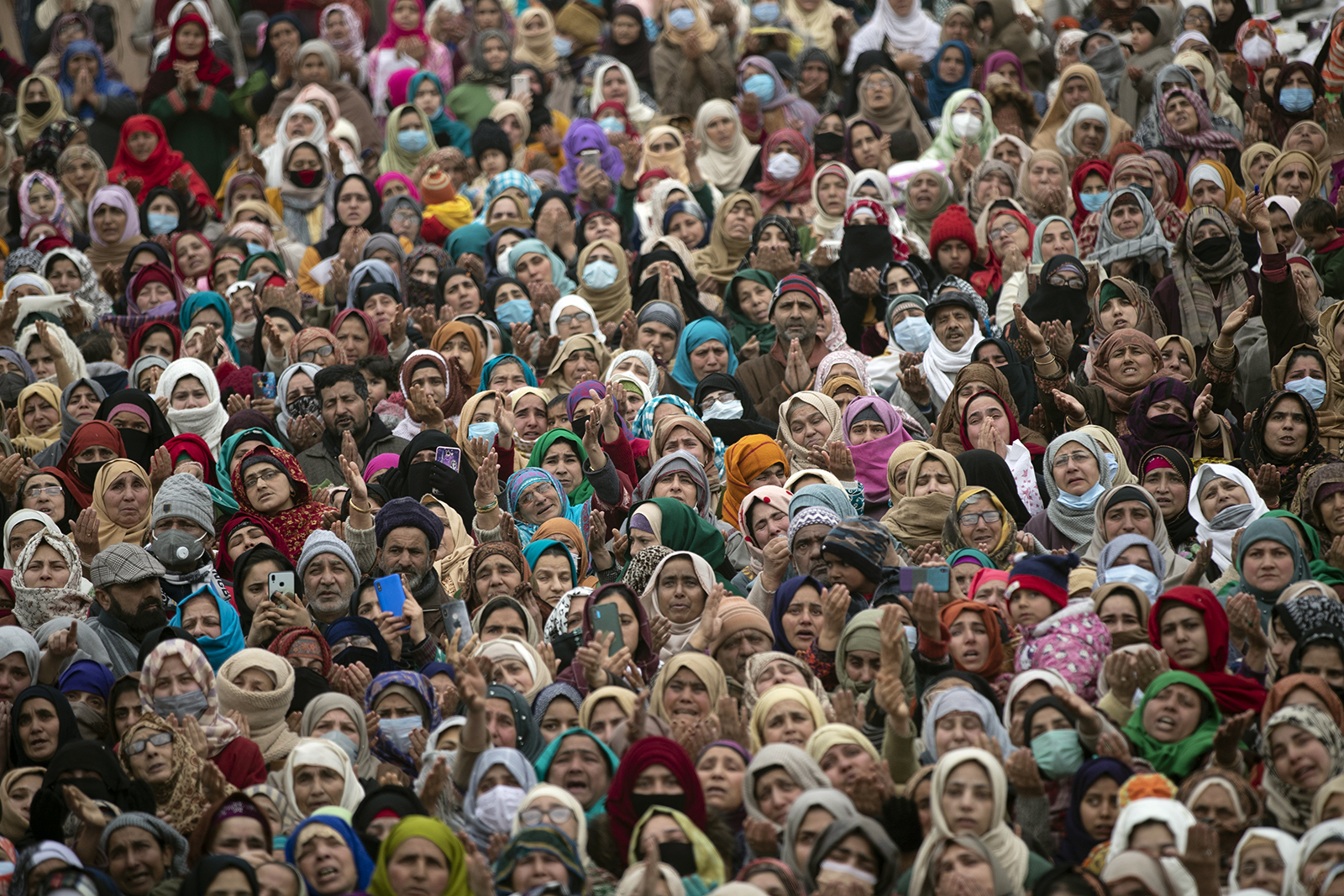 Kashmiri Muslims raise their hands and pray as the head cleric, unseen, displays a relic believed to be a hair from the beard of the Prophet Mohammad, during special prayers on the death anniversary of Abu Bakr Siddiq, the first Caliph of Islam, at Hazratbal Shrine in Srinagar, Indian controlled Kashmir, Friday, Feb. 5, 2021. (AP Photo/Mukhtar Khan)
