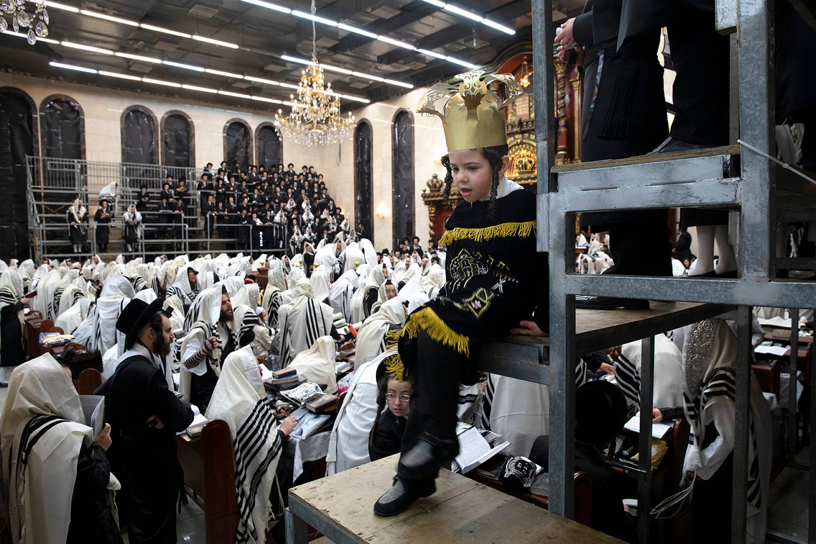 Jewish Ultra-Orthodox men and children, some wearing costumes read the Book of Esther, which tells the story of the Jewish festival of Purim, at a synagogue in Bnei Brak, Israel, Friday, Feb 26, 2021. The Jewish holiday of Purim commemorates the Jews' salvation from genocide in ancient Persia, as recounted in the Book of Esther. (AP Photo/Oded Balilty)