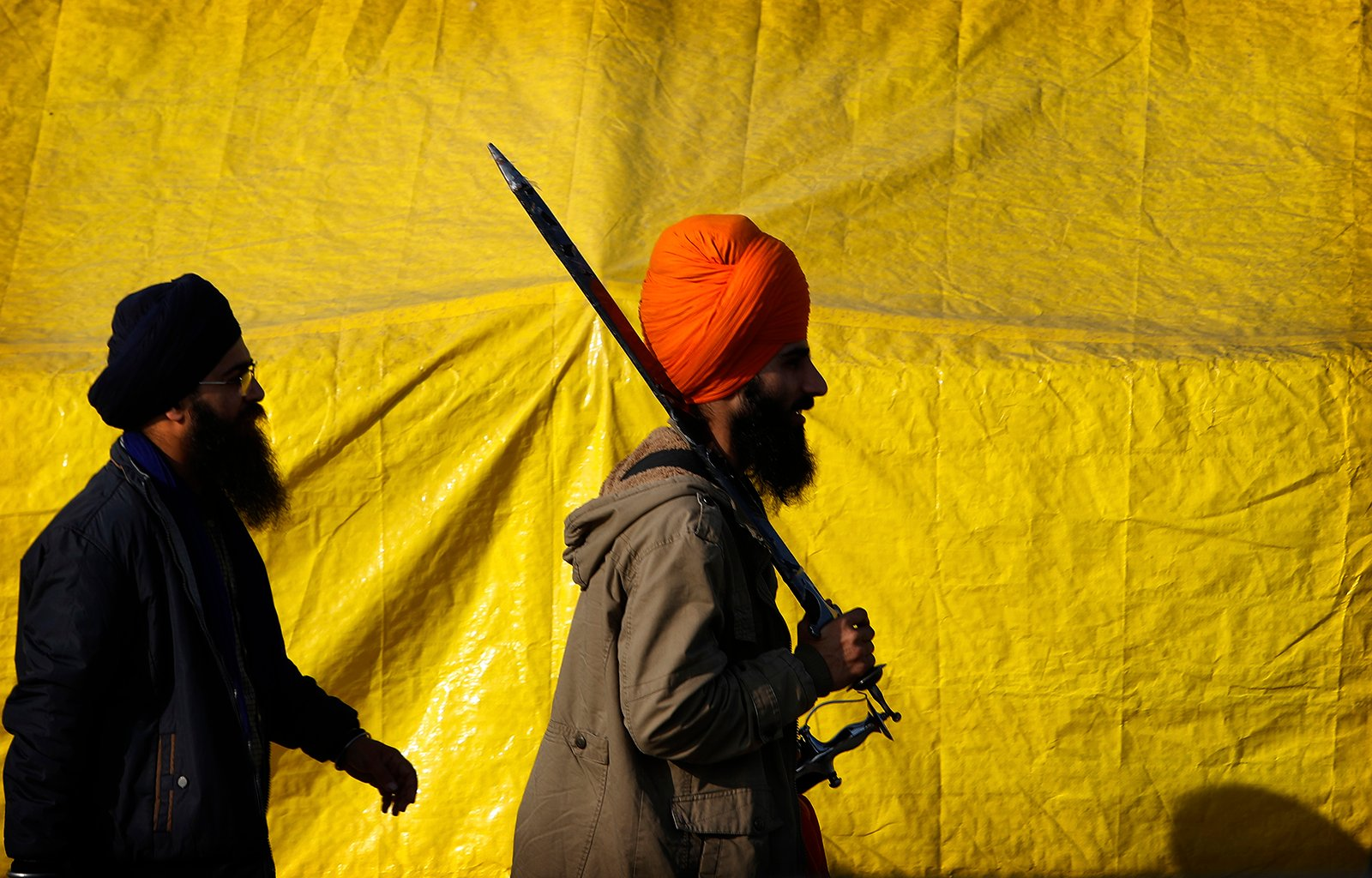 A Sikh farmer carries a sword while returning to his makeshift tent at one of the three main protest sites, at Delhi-Uttar Pradesh border, on the outskirts of New Delhi, India, Friday, Feb. 5, 2021. India's agriculture minister on Friday defended the new agriculture reform laws in Parliament, dampening hopes of any quick settlement with tens of thousands of protesting farmers demanding their repeal by blocking three highways connecting New Delhi to northern India for over two months now. (AP Photo/Manish Swarup)