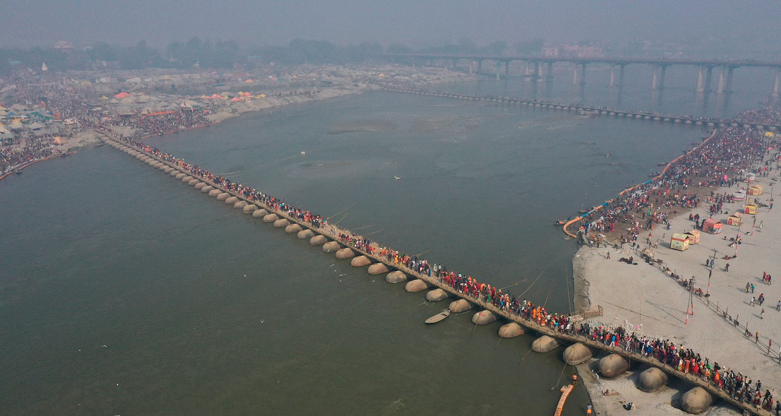 """Hindu devotees cross a pontoon bridge at Sangam, the confluence of the rivers Ganges and the Yamuna, on 'Mauni Amavasya' or new moon day, an auspicious bathing day during the annual month-long Hindu religious festival """"Magh Mela"""" In Prayagraj, India, on Thursday, Feb. 11, 2021. Hundreds of thousands of Hindu pilgrims take dips in the confluence, hoping to wash away sins during the month-long festival. (AP Photo/Rajesh Kumar Singh)"""