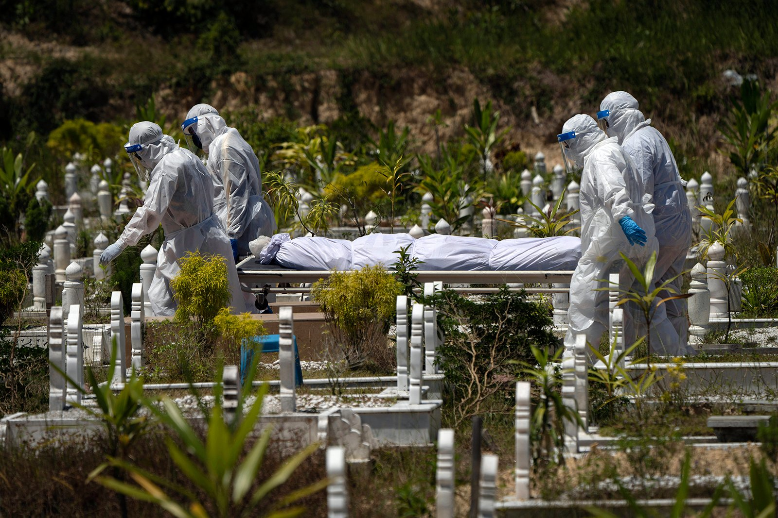 Workers wearing personal protective equipment (PPE) carry the body of a victim of the coronavirus disease at a Muslim cemetery in Gombak, outskirts of Kuala Lumpur, Malaysia, Friday, Feb. 5, 2021. The movement control order (MCO) currently enforced across the country, has been extended to Feb. 18, to try to halt the spread of the coronavirus. (AP Photo/Vincent Thian)