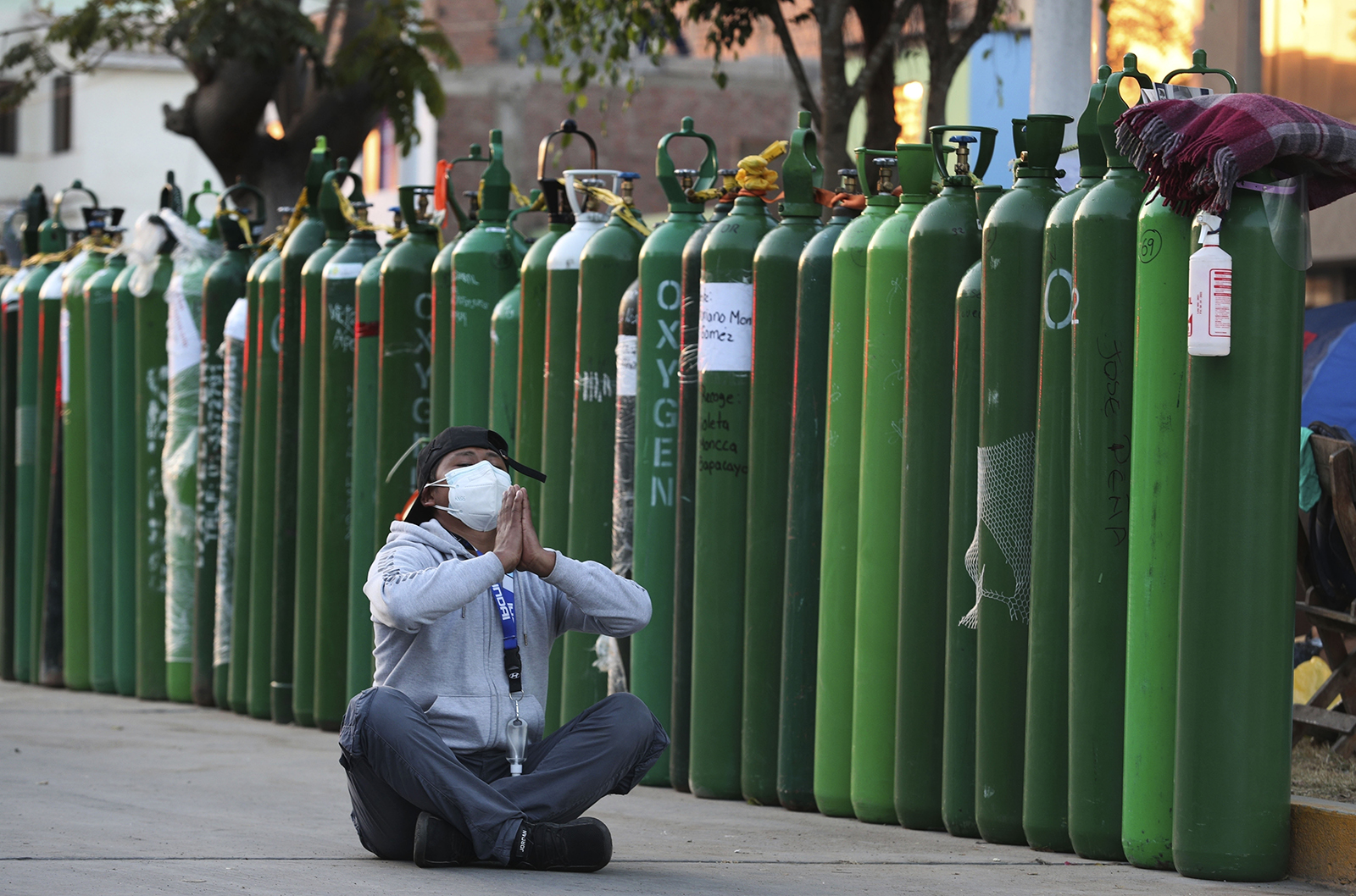 Alejandro Ccasa prays after waiting three days next to empty oxygen tanks outside a refill shop, before it opens, where he is the first in line in Callao, Peru, early Feb. 2, 2021. Ccasa was waiting to get oxygen for his uncle, who has COVID-19. His uncle died later that day. (AP Photo/Martin Mejia)