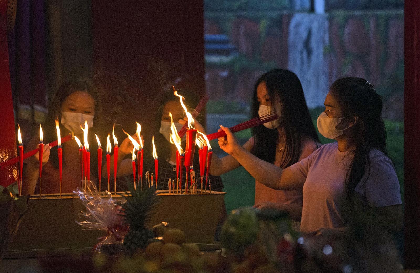 Ethnic Chinese worshippers light joss sticks during Lunar New Year's Eve celebrations at a temple in Medan, North Sumatra, Indonesia, late Thursday, Friday, Feb. 12, 2021. (AP Photo/Binsar Bakkara)