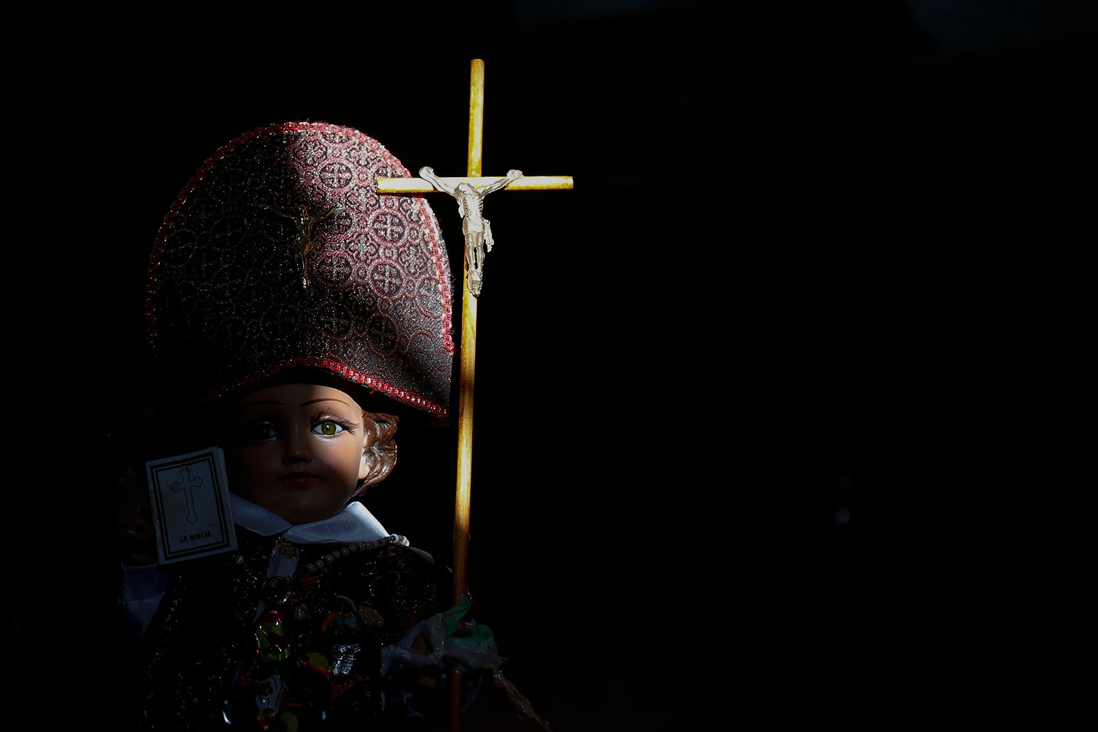 """A sunbeam shines on the face of a baby Jesus figure, held by a man waiting to have the figurine blessed, at the Purification of Our Lady of Candlemas Chapel in Mexico City, Tuesday, Feb. 2, 2021. A surge in COVID-19 cases limited celebrations of the """"Dia de la Candelaria,"""" or Candlemas Day, with Catholic Masses cancelled and families unable to gather to share the traditional holiday tamales. (AP Photo/Rebecca Blackwell)"""