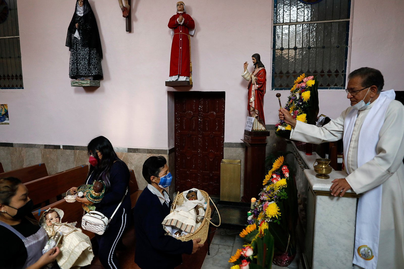 People have their baby Jesus figures blessed with holy water by Father Jose Jesus Arriaga Martinez at the Purification of Our Lady of Candlemas Chapel in Mexico City, Tuesday, Feb. 2, 2021. (AP Photo/Rebecca Blackwell)