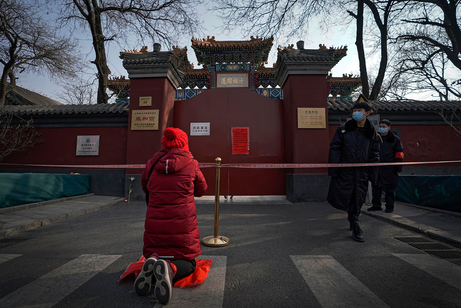 Security guards watch as a woman offers prayer near a barricade tape outside the closed Yonghegong Lama Temple, usually crowded with worshippers, during the first day of the Lunar New Year, in Beijing, China, on Friday, Feb. 12, 2021. Festivities for the holiday, normally East Asia's busiest tourism season, are muted after China, Vietnam, Taiwan and other governments tightened travel curbs and urged the public to avoid big gatherings following renewed virus outbreaks. (AP Photo/Andy Wong)