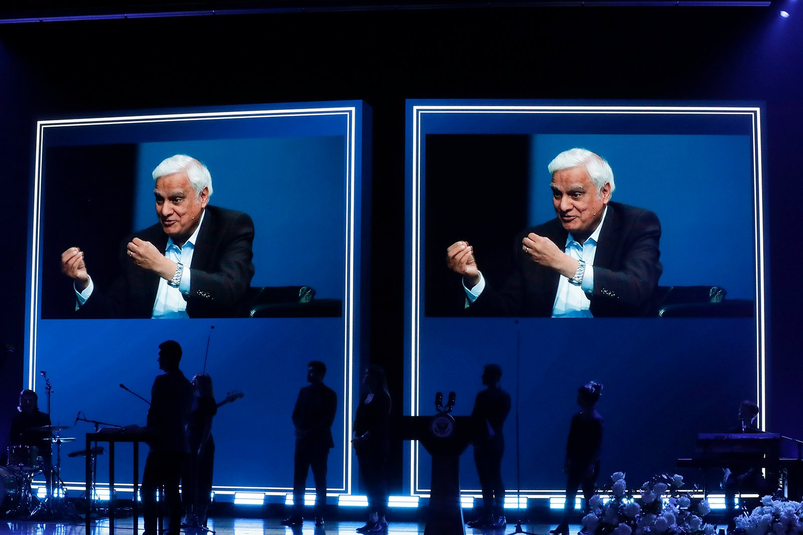 In this May 29, 2020, file photo, images of Ravi Zacharias are displayed in the Passion City Church during a memorial service for him in Atlanta. A posthumous sex scandal involving Zacharias, who founded the Ravi Zacharias International Ministries, has placed the global organization in a wrenching predicament. (AP Photo/Brynn Anderson, File)