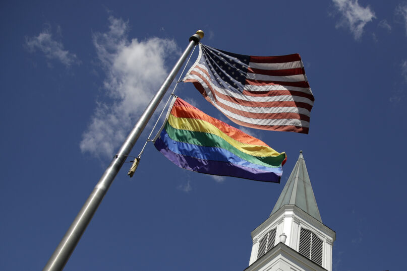 A gay pride flag flies along with the U.S. flag in front of a church in Prairie Village, Kansas, April 19, 2019. (AP Photo/Charlie Riedel)