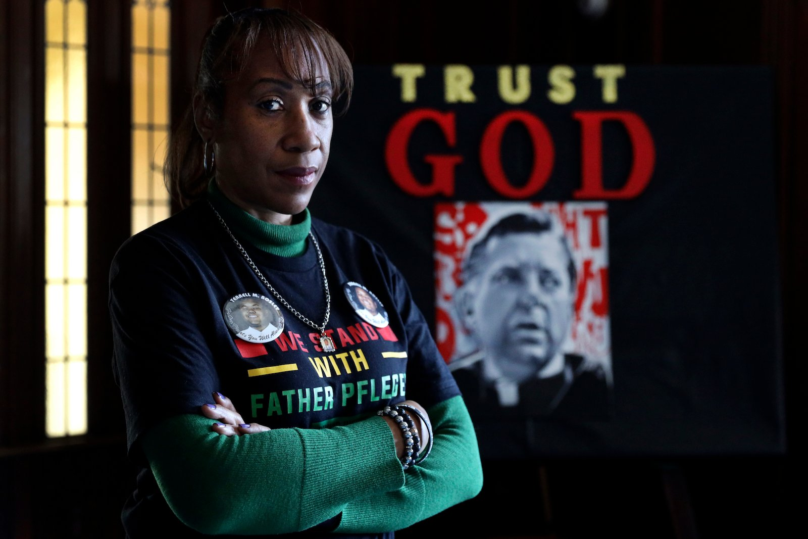 Activist Pam Bosley poses for a portrait infront of a portraiture of Father Michael Pfleger, inside the St. Sabina Catholic Church on Thursday, March 4, 2021, in Chicago. After the murder of her teenage son in 2006, Father Plfeger inspired her to become an activist, recruited her to run the South Side church's violence prevention office. (AP Photo/Shafkat Anowar)