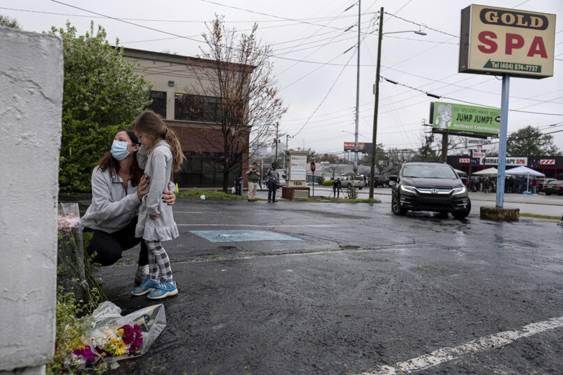 Mallory Rahman and her daughter Zara Rahman, 4, who live nearby, pause after bringing flowers to the Gold Spa in Atlanta on March 17, 2021, the day after eight people were killed at three spas in the Atlanta area. Authorities have arrested 21-year-old Robert Aaron Long in the shootings. (AP Photo/Ben Gray)