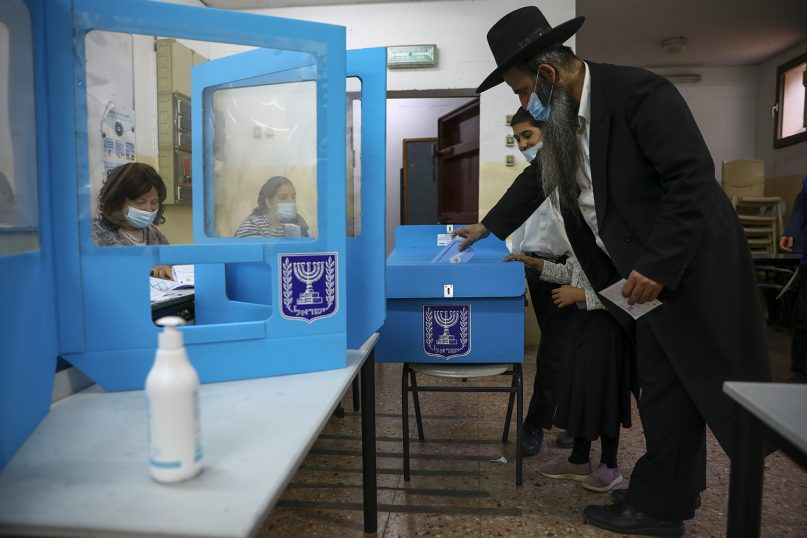 An Ultra-Orthodox Jewish man votes for Israel's parliamentary election at a polling station in Bnei Brak, Israel, Tuesday, March. 23, 2021. Israel is holding its fourth election in less than two years. (AP Photo/Oded Balilty)