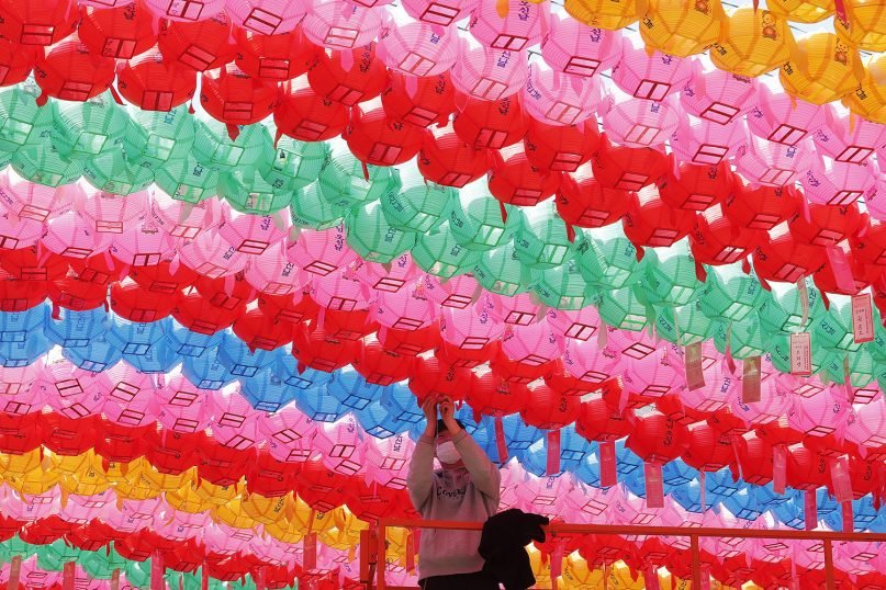 A worker wearing a face mask to help protect against the spread of the coronavirus attaches a name tag of a Buddhist who made donation to a lantern for upcoming celebration of Buddha's birthday on May 19 at Jogye temple in Seoul, South Korea, Tuesday, March 23, 2021. (AP Photo/Ahn Young-joon)