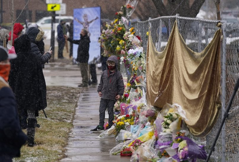 Mourners leave bouquets on a fence put up around the parking lot where a mass shooting took place the day before in a King Soopers grocery store March 23, 2021, in Boulder, Colorado. (AP Photo/David Zalubowski)