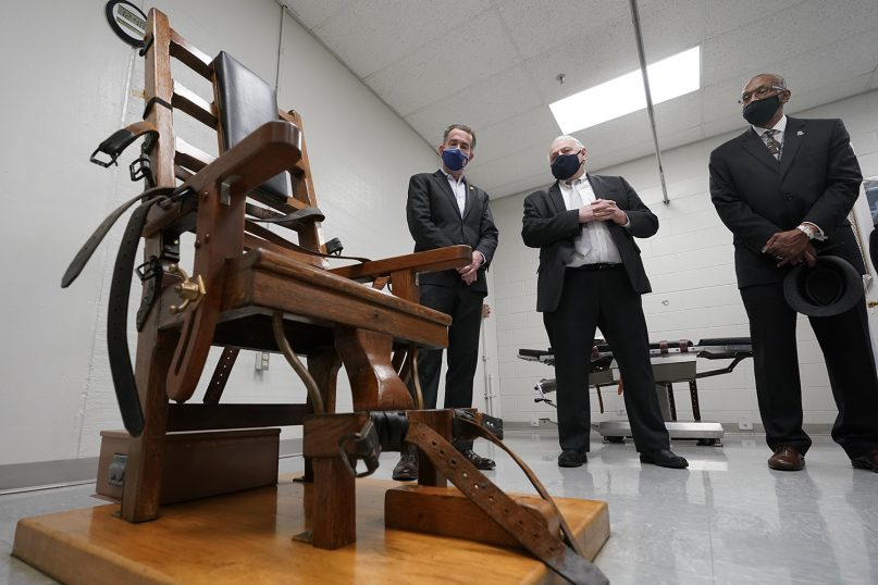 Virginia Gov. Ralph Northam, left, looks over the electric chair in the death chamber at Greensville Correctional Center with Operations Director George Hinkle, center, and Warden Larry Edmonds, right, prior to signing a bill on March 24, 2021, abolishing the death penalty in the state. (AP Photo/Steve Helber)