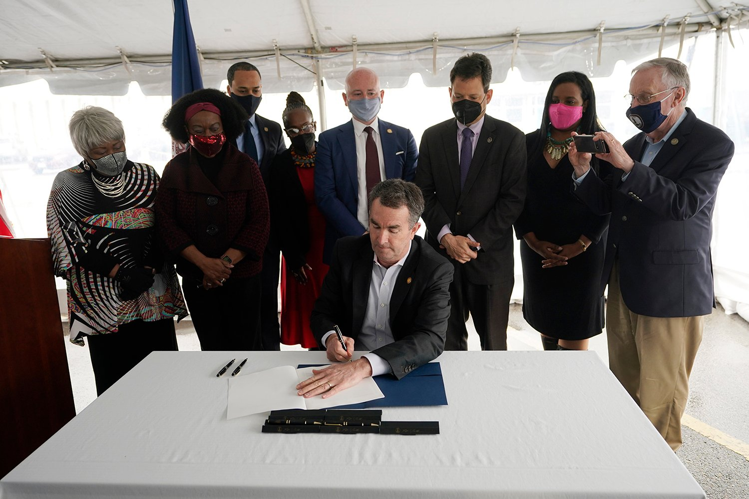 Virginia Gov. Ralph Northam, seated center, signs a bill abolishing the death penalty surrounded by legislators and activists at Greensville Correctional Center in Jarratt, Va., Wednesday, March 24, 2021. (AP Photo/Steve Helber)