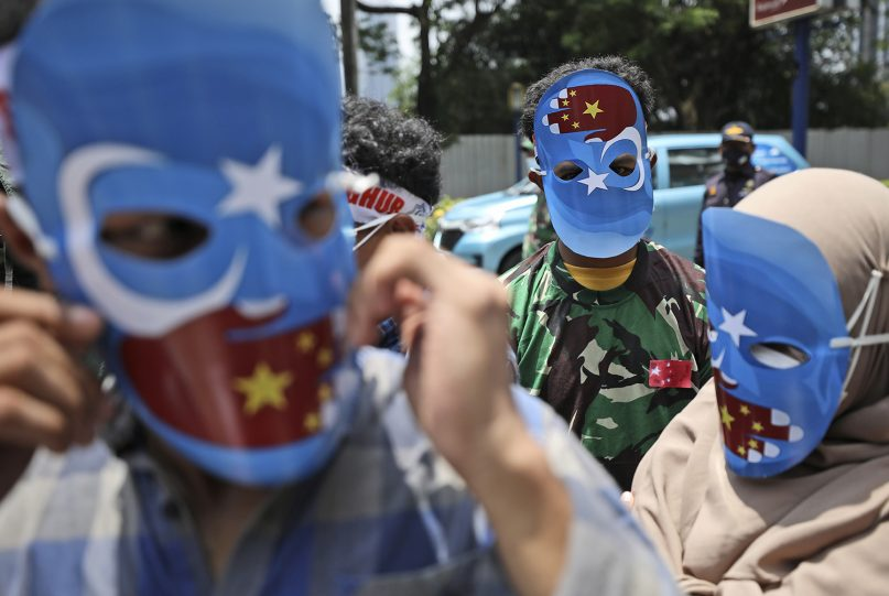 Muslim students wearing masks with the colors of the pro-independence East Turkistan flag attend a rally outside the Chinese Embassy in Jakarta, Indonesia, Thursday, March 25, 2021. About a dozen of students staged the rally calling to an end to alleged oppression against Muslim Uyghur ethnic minority in China's region of Xinjiang. (AP Photo/Dita Alangkara)