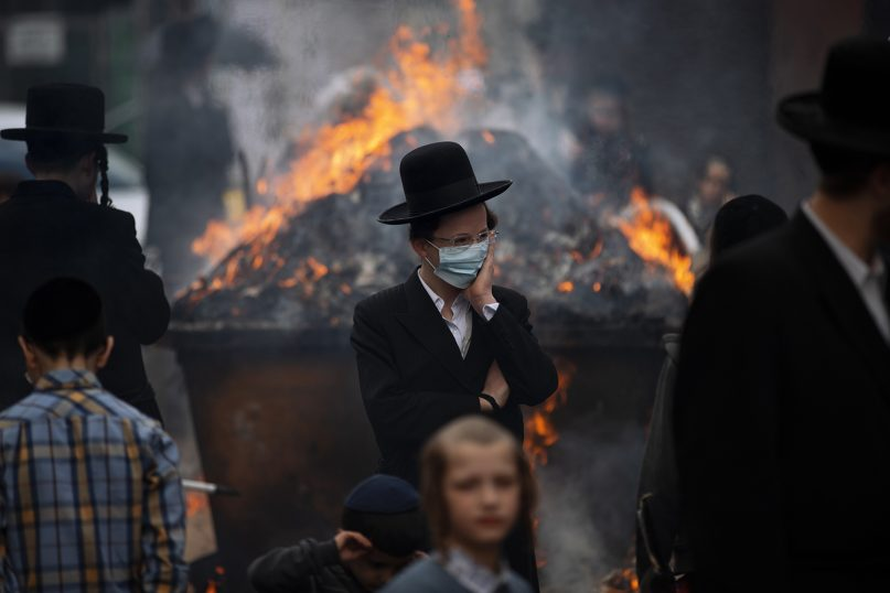 Ultra-Orthodox Jewish men and children, some wearing face mask, burn leavened items in final preparation for the Passover holiday in the ultra-Orthodox Jewish town of Bnei Brak, near Tel Aviv, Israel, Friday, March 26, 2021. Jews are forbidden to eat leavened foodstuffs during the Passover holiday that celebrates the biblical story of the Israelites' escape from slavery and exodus from Egypt. (AP Photo/Oded Balilty)