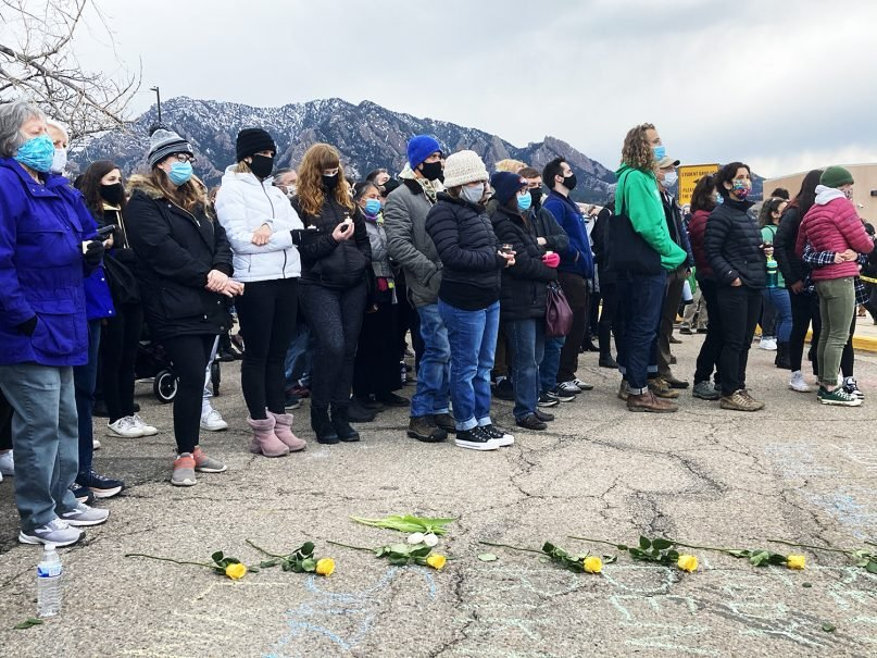 Vigil attendees gather together in the parking lot of the King Soopers in Boulder less than a day after Monday's shooting. Photo by Carina Louise Julig for RNS