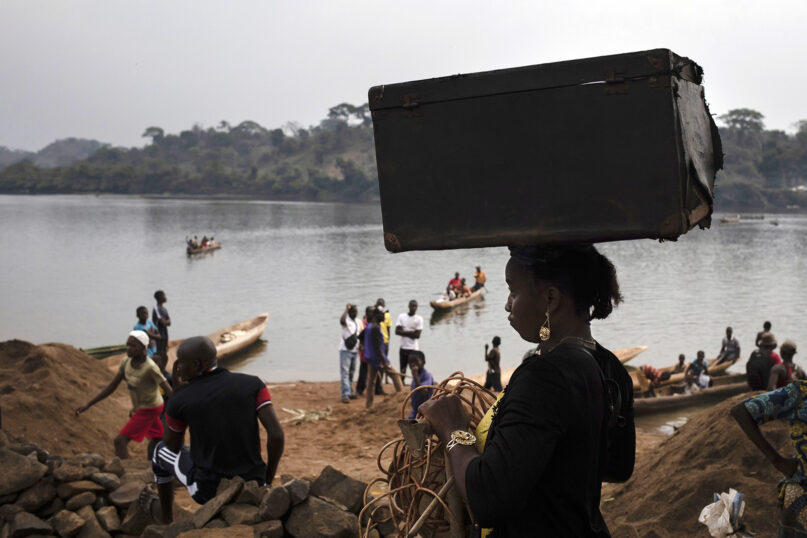 An unidentified woman carries her belongings on her head after crossing the Mbomou river back into Bangassou, Central African Republic, from Ndu in the Democratic Republic of the Congo, where she had taken refuge, Sunday Feb. 14, 2021. An estimated 240,000 people have been displaced in Central African Republic since mid-December, according to U.N. relief workers, when rebels calling themselves the Coalition of Patriots for Change launched attacks, causing a humanitarian crisis in the already unstable nation. (AP Photo/Adrienne Surprenant)