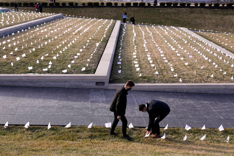 People place white flags in a plaza at the National World War I Museum, Tuesday, Jan. 19, 2021, in Kansas City, Mo. The 1,665 flags represent the area residents who have died in the coronavirus pandemic. The installation was part of a national memorial to lives lost to COVID-19. (AP Photo/Charlie Riedel)