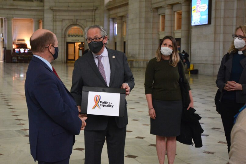 Rabbi Jack Moline, center, president of Interfaith Alliance, hands Sen. Chris Coons, D-Del., left, a group of petitions from faith leaders in support of the Equality Act, March 16, 2021, in Washington's Union Station. RNS photo by Jack Jenkins